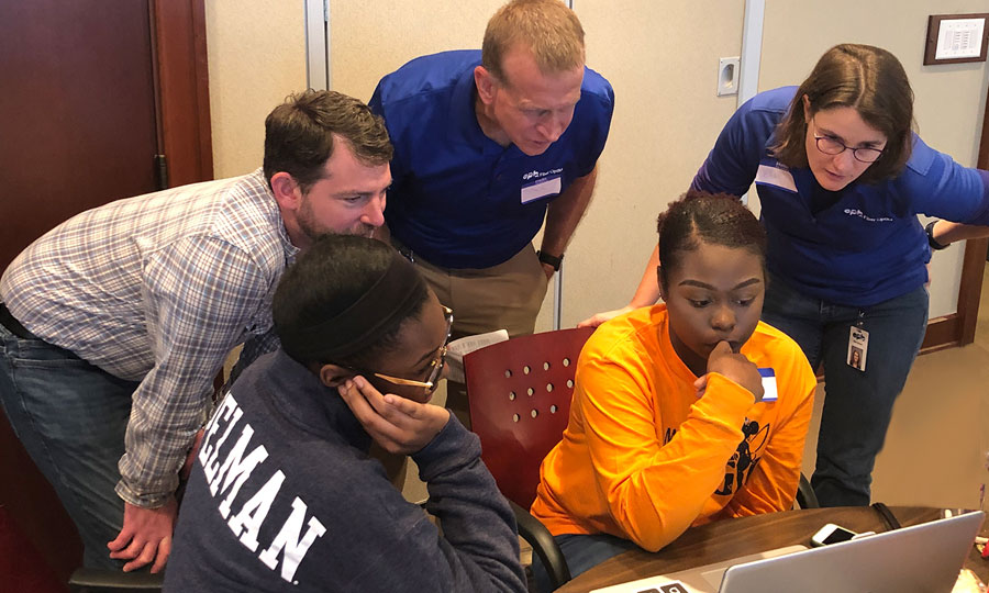 EPB employees helping student on laptop